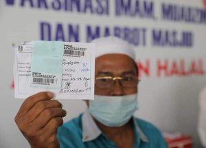 Salah satu imam masjid yang menunjukkan sertifikat usai divaksin di Masjid Al-Akbar, Surabaya. (Istimewa/ Humas Pemprov Jatim )